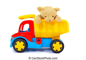 Stuffed toy bear riding in the back of a colorful toy dump truck. Isolated on white background.