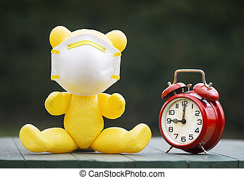 Toy bear with protection mask and alarm clock, lockdown, ...