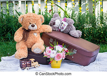 Toy bears sitting on suitcases