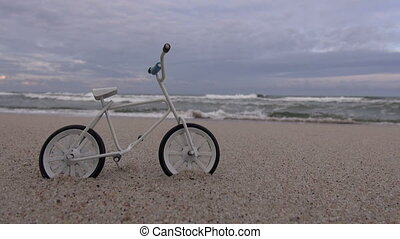 Toy bicycle model on the beach