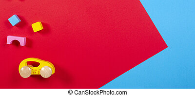 Toy car and wooden blocks on colorful background