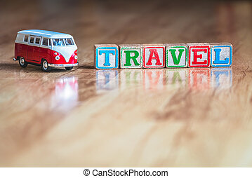 Toy car and wooden blocks spellling travel
