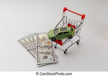 Toy car in a shopping basket and dollar banknotes