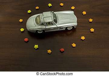 toy car in sugar stars in form circle on wooden background