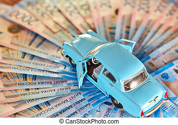 Toy car on a background of Russian money. Concept of auto insurance and fuel prices