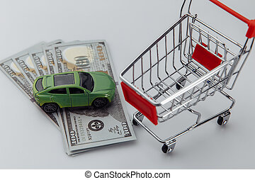 Toy car, shopping basket and dollar banknotes on a white background. Close-up