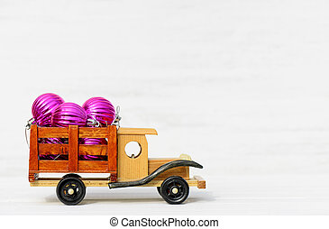 Toy car with Christmas toys on a woden white background