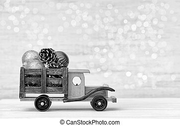 Toy car with Christmas toys on a woden white background with bokeh. Black and white image