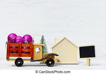 Toy car with Christmas toys, wooden house and tree on a woden white background