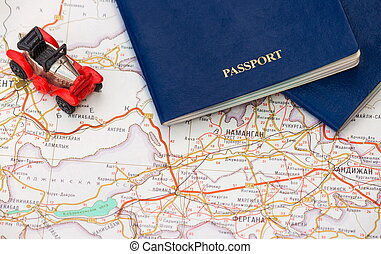 Toy car with two passports on the background of the map