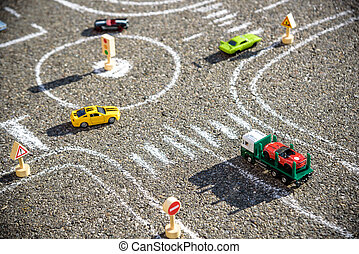 Toy cars red green blue color on the road chalked on black asphalt. Difficult traffic rules concept.