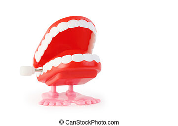 toy clockwork open jaw with white teeth on pink legs on white background