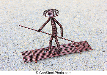 toy crafts boatman made of copper wire on the ground