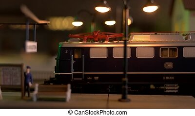 Toy diesel locomotive leaving the station. Miniature passenger train moving on mini railroad. Miniature of railway station.