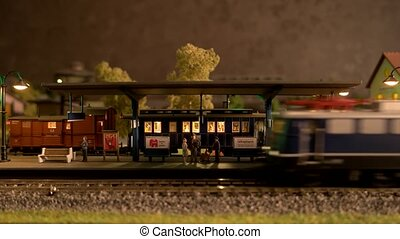 Toy diesel locomotive moving through model railway station. Toy trains for children. Play with fun.