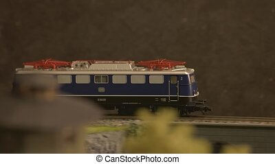 Toy diesel railway locomotive moving through forest. Model of diesel locomotive in motion. Mini train station modeling.