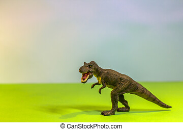 Toy dinosaur in a toy forest. like a real T-rex on a bright studio background with wooden trees. Eco toys.