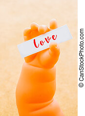 Toy doll hand holding paper with the word LOVE