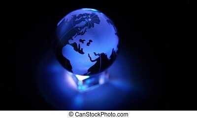 Toy Earth sphere stand on cube with color illumination, composition spins