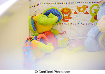 Toy elephant sat in a baby crib