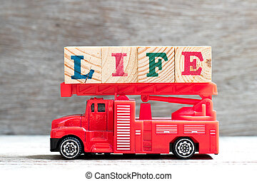 Toy fire ladder truck hold letter block in word life on wood background