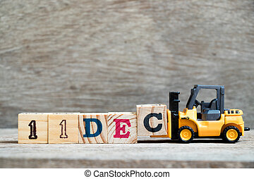 Toy forklift hold block c to complete word 11dec on wood background (Concept for calendar date 11 in month December)