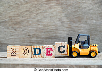 Toy forklift hold block c to complete word 20dec on wood background (Concept for calendar date 20 in month December)