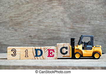 Toy forklift hold block c to complete word 31dec on wood background (Concept for calendar date 31 in month December)