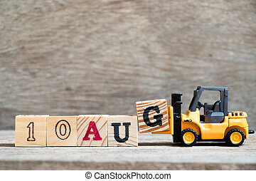 Toy forklift hold block G to complete word 10 aug on wood background (Concept for calendar date in month August)