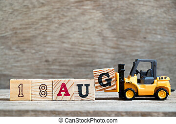 Toy forklift hold block G to complete word 18 aug on wood background (Concept for calendar date in month August)