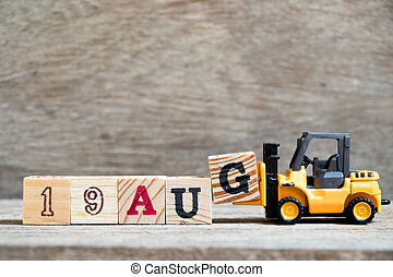 Toy forklift hold block G to complete word 19 aug on wood background (Concept for calendar date in month August)