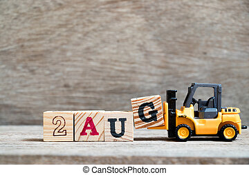 Toy forklift hold block G to complete word 2 aug on wood background (Concept for calendar date in month August)