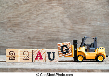 Toy forklift hold block G to complete word 22 aug on wood background (Concept for calendar date in month August)