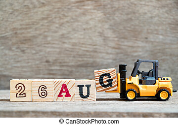 Toy forklift hold block G to complete word 26 aug on wood background (Concept for calendar date in month August)