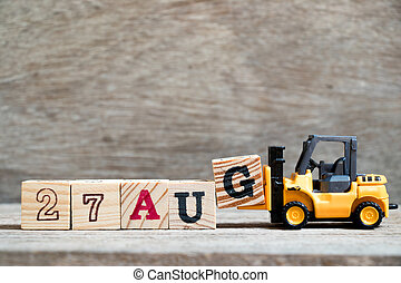 Toy forklift hold block G to complete word 27 aug on wood background (Concept for calendar date in month August)