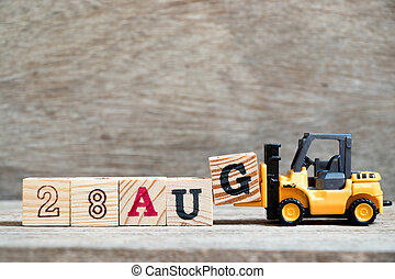 Toy forklift hold block G to complete word 28 aug on wood background (Concept for calendar date in month August)