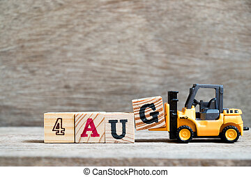 Toy forklift hold block G to complete word 4 aug on wood background (Concept for calendar date in month August)