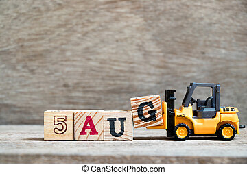 Toy forklift hold block G to complete word 5 aug on wood background (Concept for calendar date in month August)