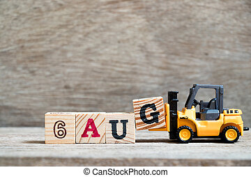 Toy forklift hold block G to complete word 6 aug on wood background (Concept for calendar date in month August)