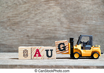 Toy forklift hold block G to complete word 8 aug on wood background (Concept for calendar date in month August)