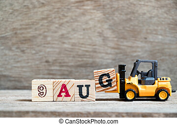 Toy forklift hold block G to complete word 9 aug on wood background (Concept for calendar date in month August)