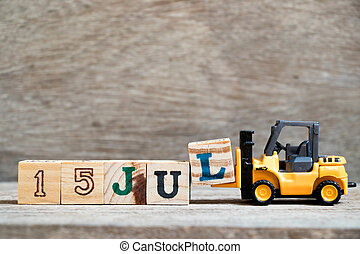 Toy forklift hold block l to complete word 15 jul on wood background (Concept for calendar date in month July)