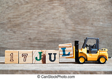Toy forklift hold block l to complete word 17 jul on wood background (Concept for calendar date in month July)