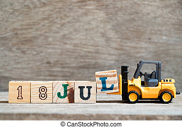 Toy forklift hold block l to complete word 18 jul on wood background (Concept for calendar date in month July)