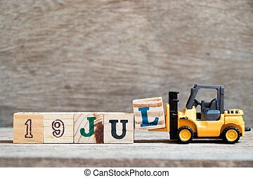 Toy forklift hold block l to complete word 19 jul on wood background (Concept for calendar date in month July)