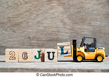 Toy forklift hold block l to complete word 26 jul on wood background (Concept for calendar date in month July)