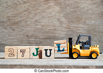 Toy forklift hold block l to complete word 27 jul on wood background (Concept for calendar date in month July)