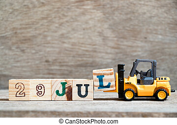 Toy forklift hold block l to complete word 29 jul on wood background (Concept for calendar date in month July)
