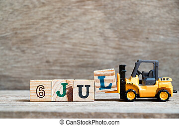 Toy forklift hold block l to complete word 6 jul on wood background (Concept for calendar date in month July)