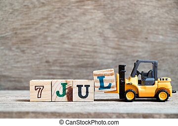 Toy forklift hold block l to complete word 7 jul on wood background (Concept for calendar date in month July)
